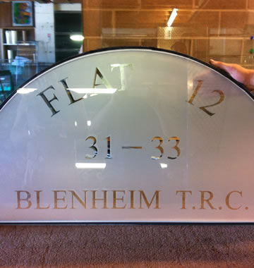 A custom arched glass pane for a door that has house number
